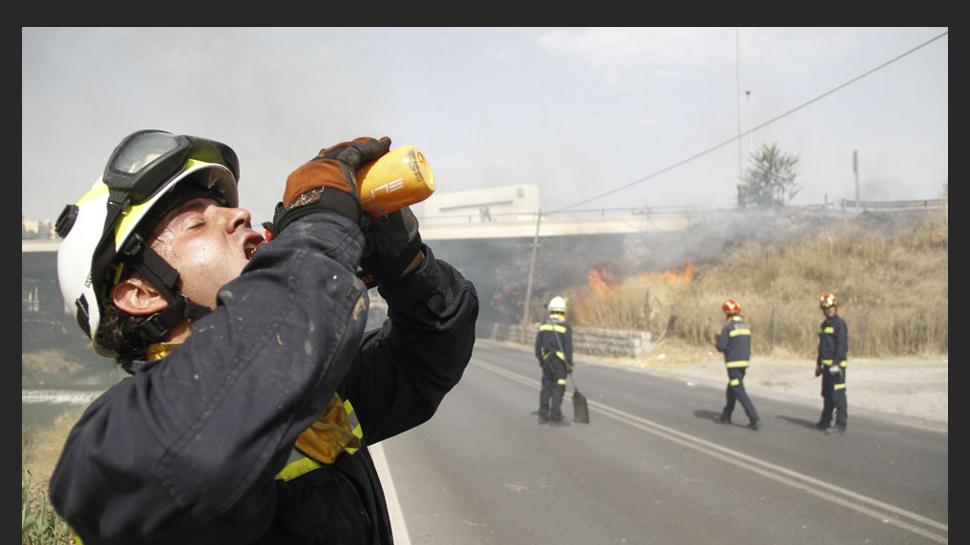 1 DE JULIO. Las altas temperaturas obligaron a los bomberos a tener que intervenir en numerosos incendios tanto forestales como urbanos, entre ellos uno ubicado en la carretera que comunica Granada capital con Las Gabias. En la imagen, uno de los bomberos consume agua para reponer fuerzas ante tal ardua tarea. [LEER NOTICIA]