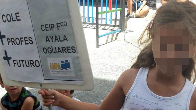 Una de las niñas portando una pancarta a las puertas del colegio. Foto: aG